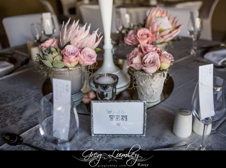 Rustic and classy wedding reception layout using pink proteas, roses and metal buckets