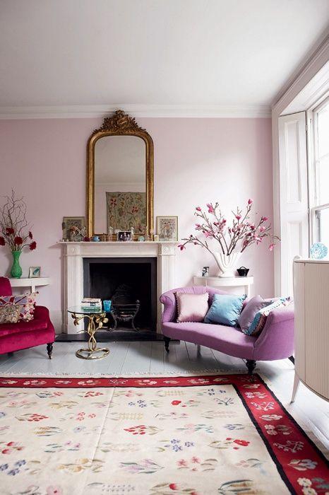 Гостиная выкрашена в цвет розового жемчуга. По мнению Лулу, он создает романтическую атмосферу и выгодно оттеняет позолоченное зеркало и бархатное кресло цвета сливы. Подушка с помпонами, The Rug Company. Старый диван получил второе рождение благодаря обивке из льна, Designers Guild, и подушкам, сшитым Лулу.