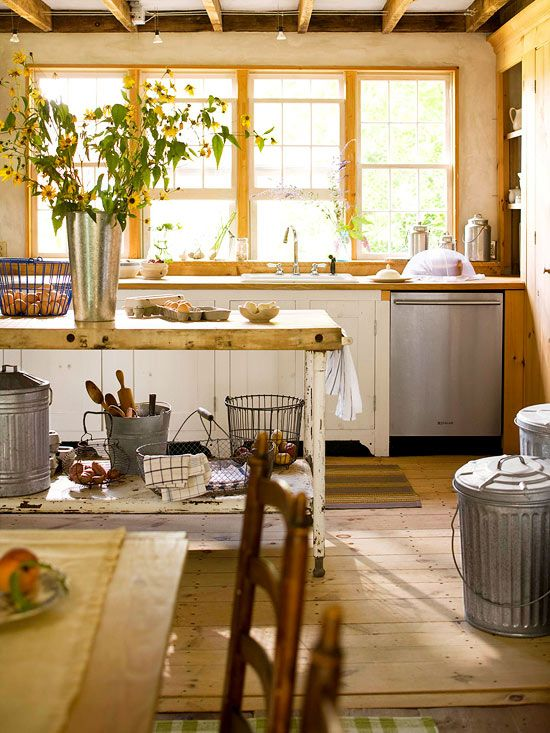 Exposed upper-level floor joists and six-over-six windows above the kitchen's sink beckon sun and warmth. A floor-to-ceiling pantry and floor made of pine gives the farmhouse space a rustic feel.