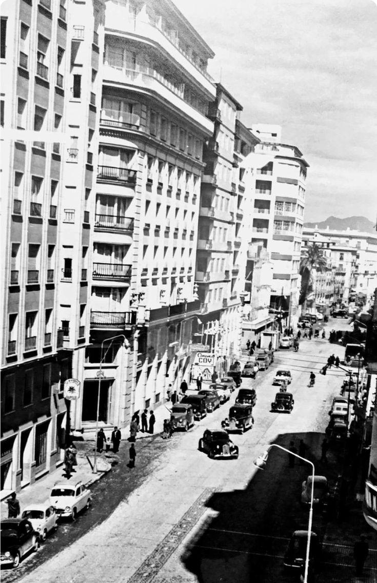 Murcia, Finales de los años 50. Una Gran Vía en plena transformación..!!! Los primeros y modernos rascacielos murcianos, junto con los automóviles de los 40-50, los primeros Seat, y las Galeras taxi, todavía confluyen durante algunos años más, en armonía..!! Murcia