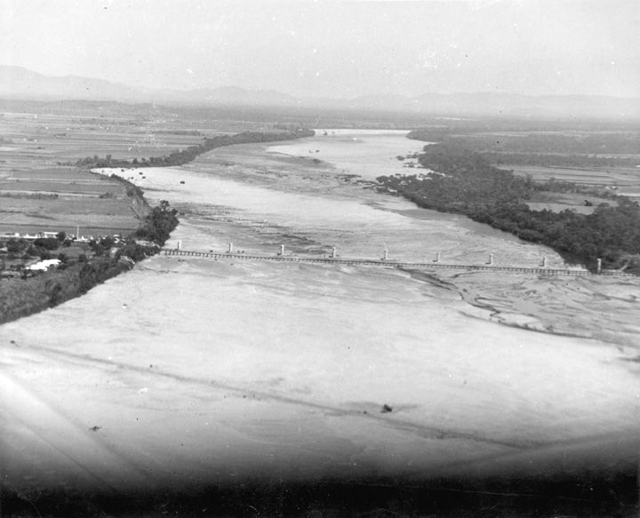 Aerial photograph of Burdekin Bridge construction site showing piers, with Railway Bridge in foreground, c1952. Queensland State Archives.
