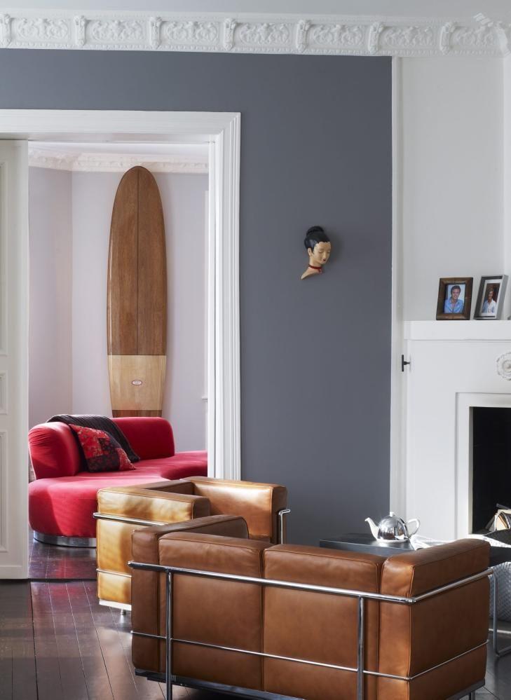 NOSTALGI: Et klassisk surfebrett i mahogni er blitt til veggpynt. Salongen fra Le Corbusier glir fint inn i interiøret. En rød sofa skaper spenning.