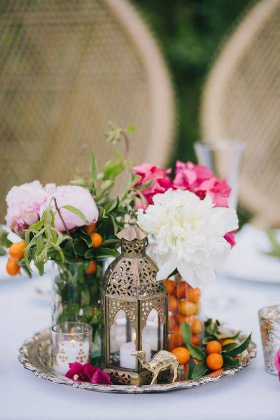 Create a dynamic centerpiece display by gathering a handful of thematic elements within a basic tray. This Moroccan-inspired arrangement features a mini ornate lantern, a couple of vases of blush-toned peonies, a tea light votive, and a camel figurine. Bright orange kumquats lend a pop of color and the perfect finishing touch to the display.