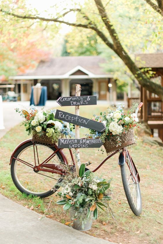 bike adorned with flowers and a directional sign for guests / http://www.himisspuff.com/bicycle-wedding-ideas/