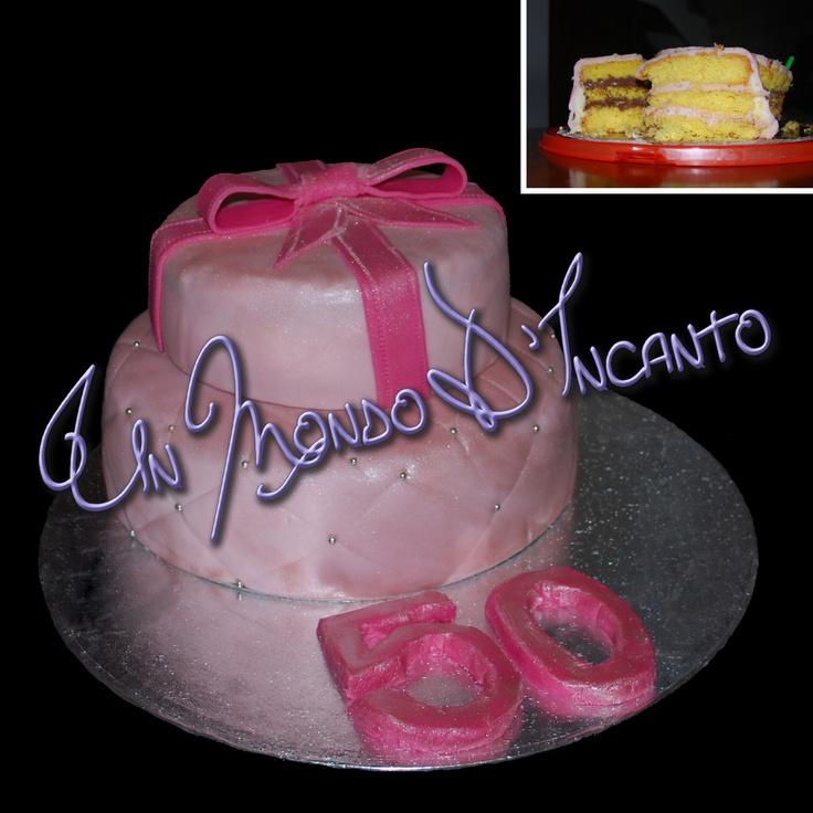 """Torta """"Pacchetto Regalo Rosa"""" a due piani per i 50 anni di Mimma.  Piano superiore farcito con crema alla fragola, piano inferiore con crema alla nutella, il tutto ricoperto e decorato con pasta di zucchero."""