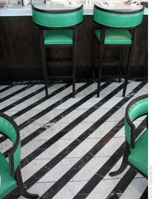 Green chairs and black and white striped floor.