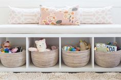 Alyssa Rosenheck - Amanda Barnes Interior Design - Ethereal girl's nursery features a white freestanding storage bench filled with gray woven baskets and lined with pink trellis pillows placed under a window.