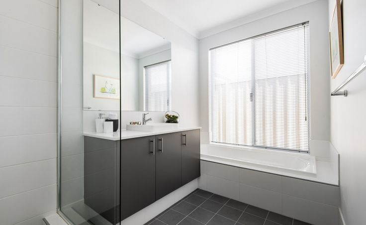 The main bathroom offers Caesartone benchtops with semi-inset vanity basins, mixer taps and glass semi-frameless pivot screen doors