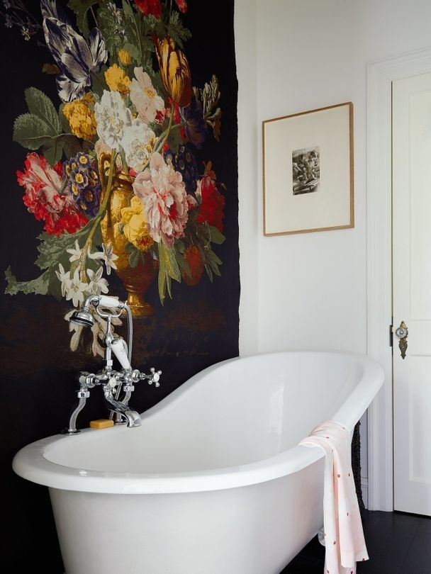 Inside Simone Rocha's art-filled terrace home: This floral tapestry creates a beautiful, feminine mood in the bathroom with a traditional claw foot bath and old fashioned door handles.