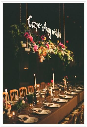 A mesa dos noivos, em um casamento no campo, com elementos de madeira e muitas flores, além do toque moderno com o letreiro suspenso.