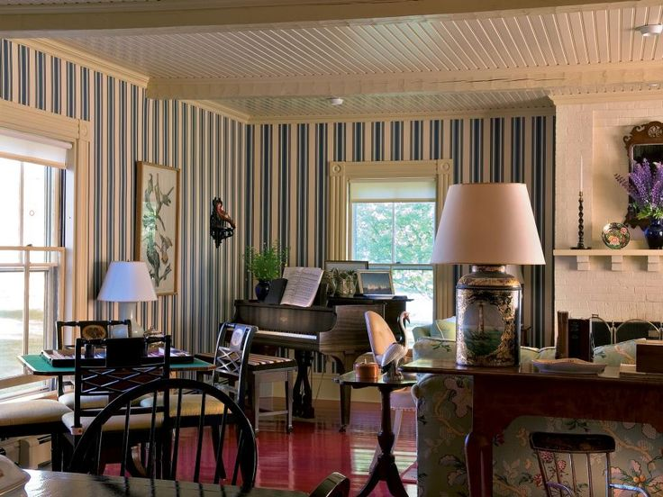 Red Hardwood in British Colonial | This living room evokes the nautical with a red, white and blue color palette. A white tongue-and-groove ceiling looks down upon a high-gloss red hardwood floor, while blue-and-white striped wallpaper lines the walls. Dark Colonial furniture, avian accessories and exotic floral upholstery are a nod to tropical style.