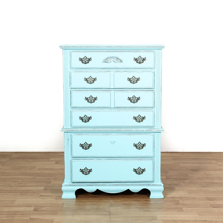 This tall dresser is featured in a solid wood with an aqua blue paint finish. This shabby chic style chest of drawers has 6 graduated drawers, carved trim, and ornate hardware. Perfect for storing clothing and accessories! #shabbychic #dressers #talldresser #sandiegovintage #vintagefurniture