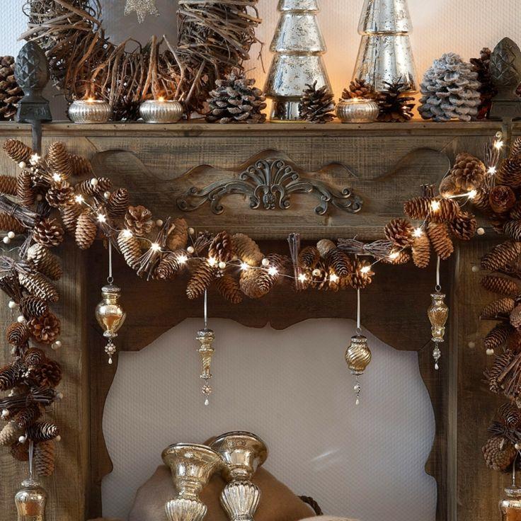 chimenea con luces navideñas y guirnalda de piñas