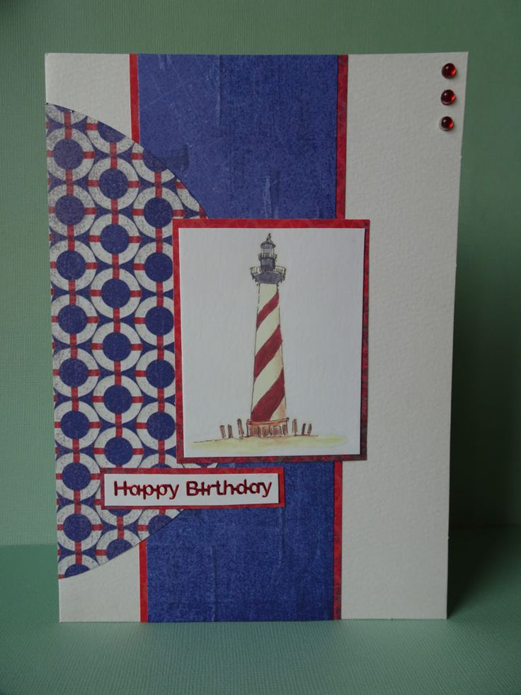 White card with a light house image and nautical papers including life buoy