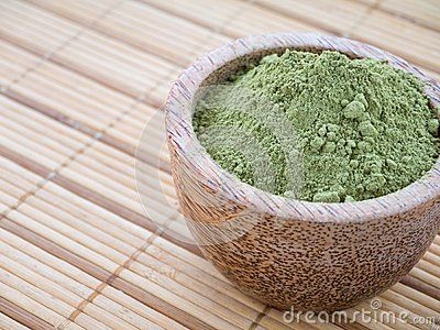 Henna powder in the coconut bowl on the bamboo mat background