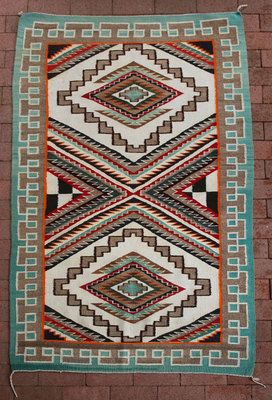 Teec Nos Pos style rug.  Use of contrasting colours to outline elements.  (Unknown origin to style. Persian influence. Trader H.B. Noel said the influence was from a missionary.)