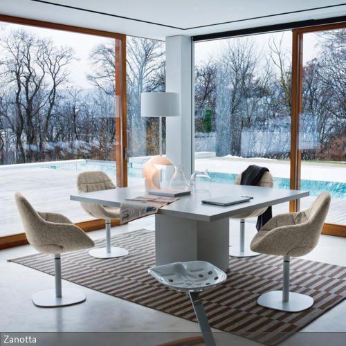 Der einbeinige Esstisch passt sich durch seine eckige Form harmonisch an die Ecke der Fensterfronten an. Stoffbezogene, organisch geformte Esszimmerstühle bilden…