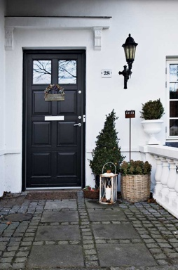 studio karin: Exteriör FASAD o ENTRÉ. Black classic door, entrance, facade, hurricane lamp, wicker, white fence
