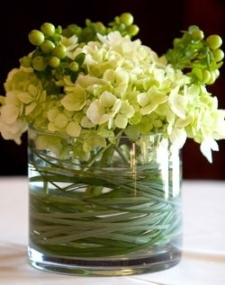 Center piece of green hydrangea and hypericum berries with bear grass swirled around the inside of the vase