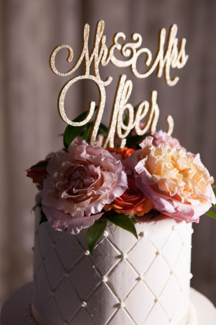 A fabulous gold glitter script wedding cake topper to accentuate the floral wedding cake topper (Carrie Wildes Photography)