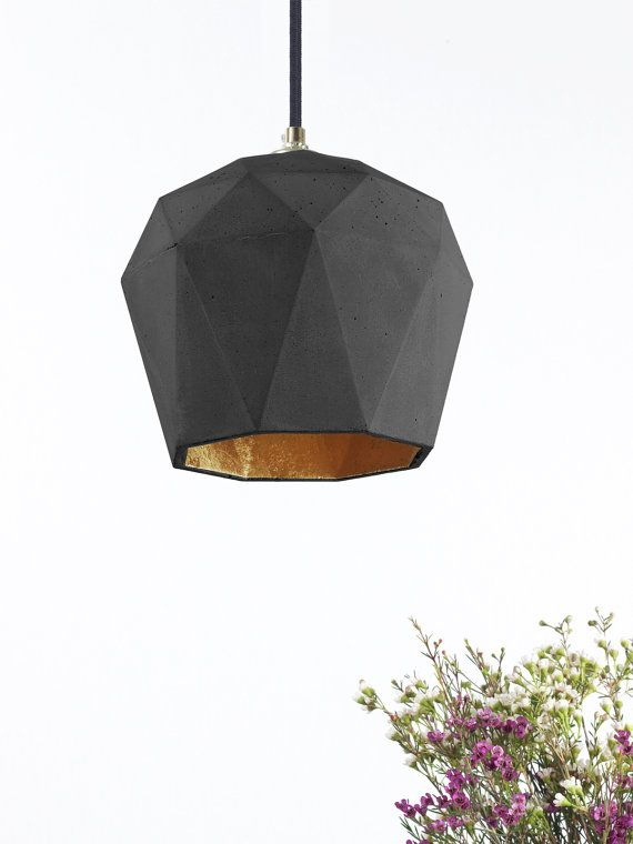 [T3]dark  The triangulated hanging lamp [T3]dark is cast from darkgray concrete . It combines noble gold with rough concrete into a timeless and