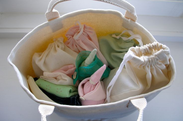 Tiny dolls with a range of small complimentary collections stored in drawstring bags.