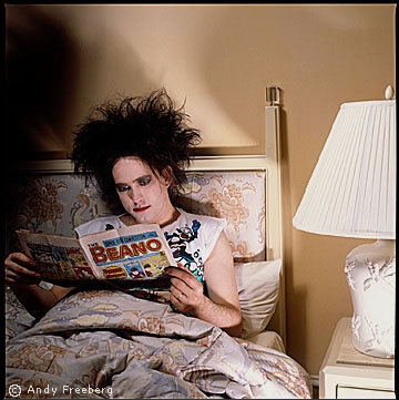 Robert Smith from The Cure reading comics in bed