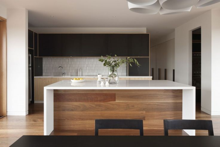 wood floors and white kitchen benchtop contrasted with black dining table and shairs and