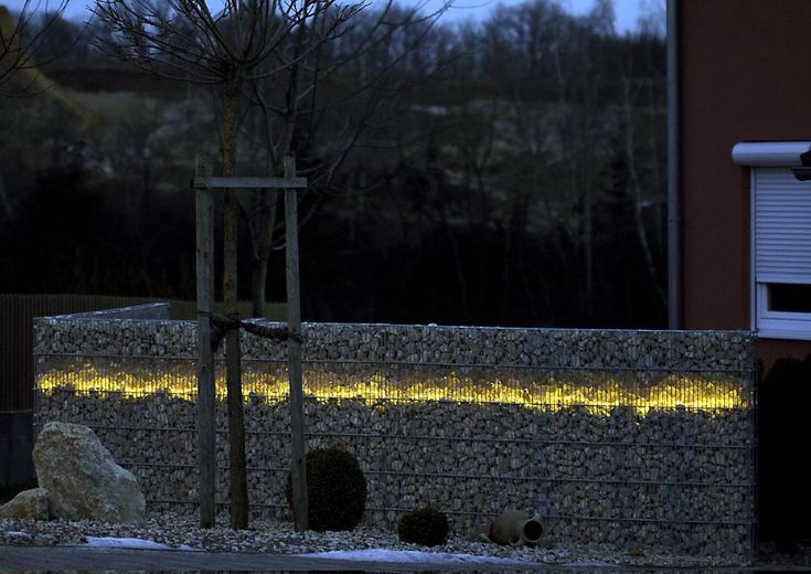 Rock gabions with a stripe of glass rocks and rope light.