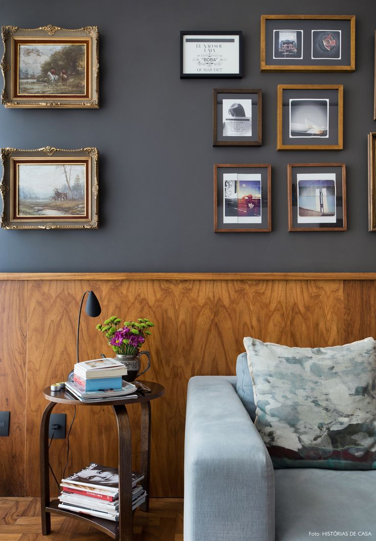 Lambri de madeira, parede cinza e galeria de quadros.