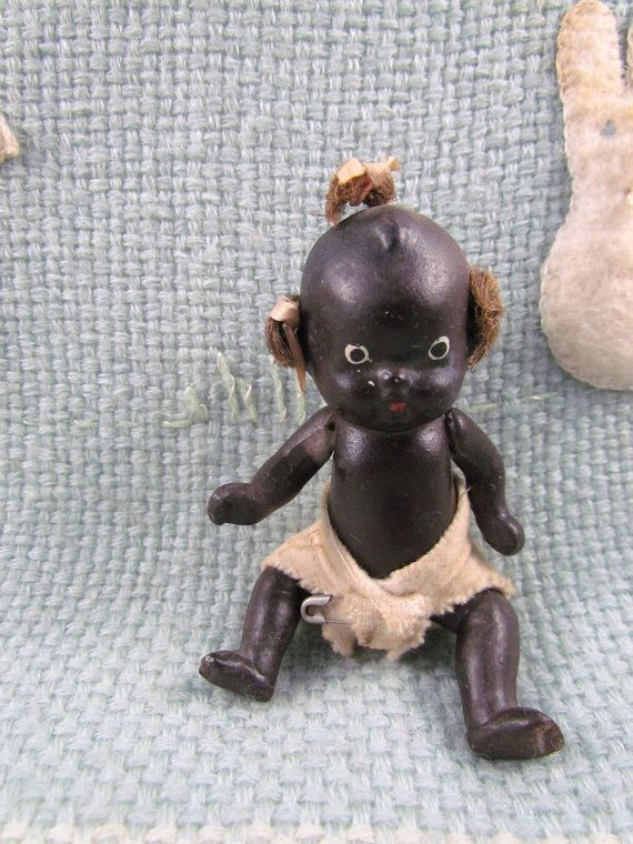 Collectible Black baby doll with jointed arms legs and rooted hair made from jute or twine all hand painted imported from Japan around the 1930's flannel diaper with safety pin in good condition