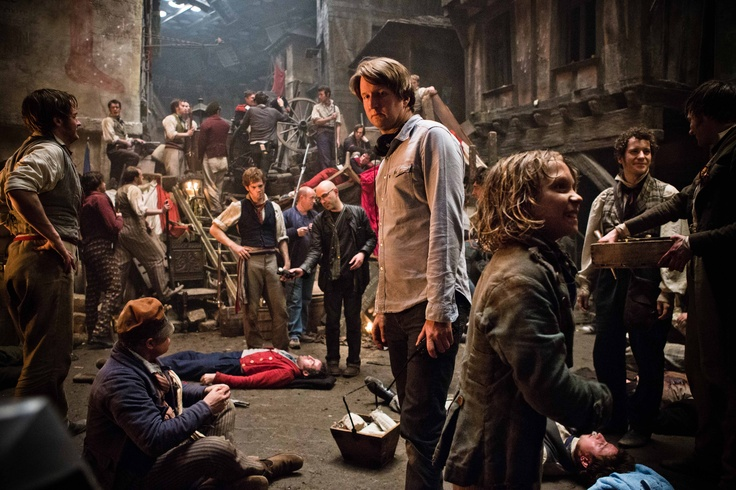 """(Center) Oscar®-winning director TOM HOOPER and DANIEL HUTTLESTONE as Gavroche on the set of """"Les Misérables"""", the motion-picture adaptation of the beloved global stage sensation seen by more than 60 million people in 42 countries and in 21 languages around the globe and still breaking box-office records everywhere in its 28th year."""