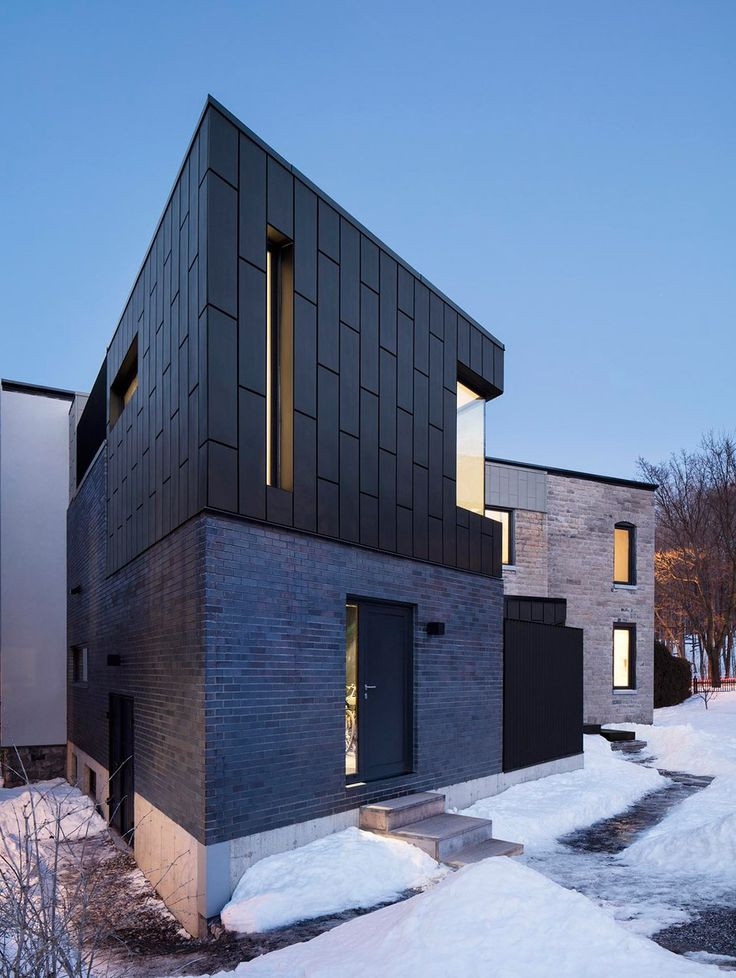 Dark zinc-clad extension added to historic dwelling in Montreal
