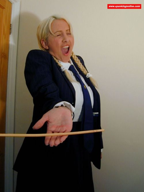 discipline-matters:  Looks like she is feeling it, but extremely casual.  Maintaining good eye contact, and holding the hand out properly is all part of the punishment.
