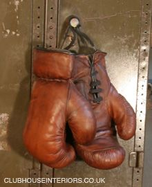 a pair of Restored Vintage Leather Boxing Gloves hanging on a Military Style Antique Metal Locker. Vintage Gym Equipment, Antique Sports Equipment, Unique Shop Display Props, Restored Sports Equipment, Antique Furniture, Vintage Furniture. - Clubhouse Interiors