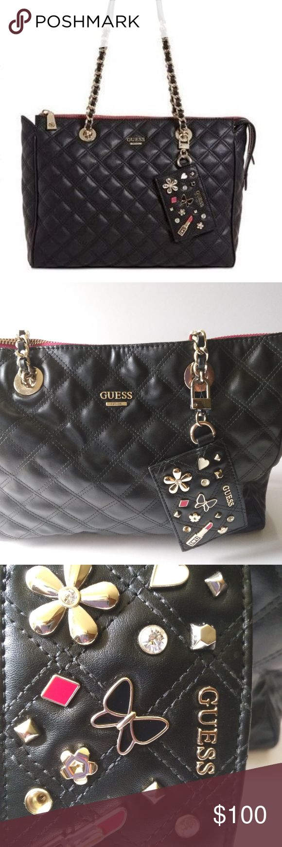 """GUESS Darin Extra-Large Carryall Black A fun hanging logo charm adds playful polish to this versatile GUESS carryall shaped from soft and smooth quilted faux leather and detailed with shining metallic hardware with a chain strap. Few times used, very good condition, one diamond missing from logo charm Extra-Large sized bag; 16-1/2""""W x 11""""H x 3-3/4""""D 11""""L chain-detail double handles Zip closure Pale shiny gold-tone exterior hardware, logo, hanging charm, feet & 1 zip pocket Guess Bags…"""