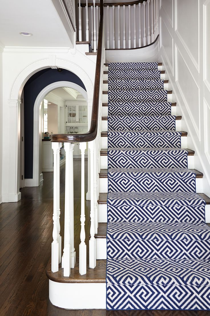 Navy and White geometric runner by Stark Carpet for this classic 1920's home. Custom White wall paneling and painted white risers. Navy pocket wall with arched opening. Designed by SHOPHOUSE Interiors. www.shophousedesign.com