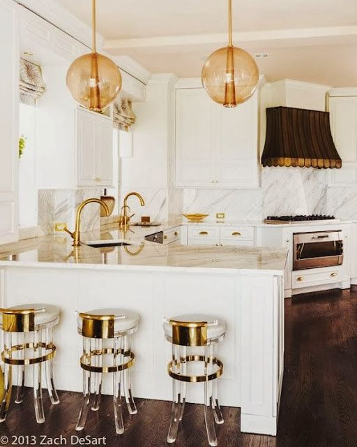 South Shore Decorating Blog: awning type brass range hood and lucite stools with marble and brass...oh my