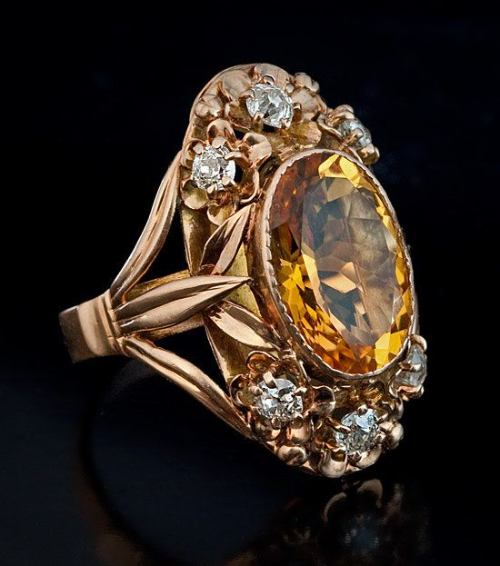 Russian, circa 1910    The 14K rose gold ring of an openwork Art Nouveau floral design is bezel set with an oval citrine (14.5 x 10 x 6.5 mm,