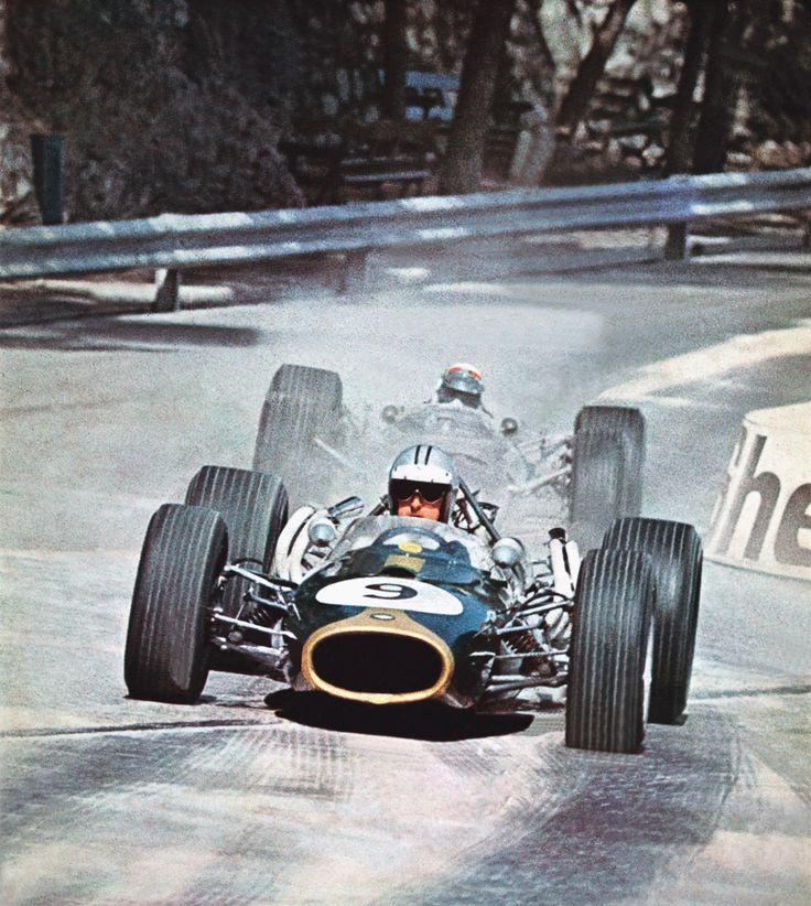 Denis Hulme with Jackie Stewart right behind him.