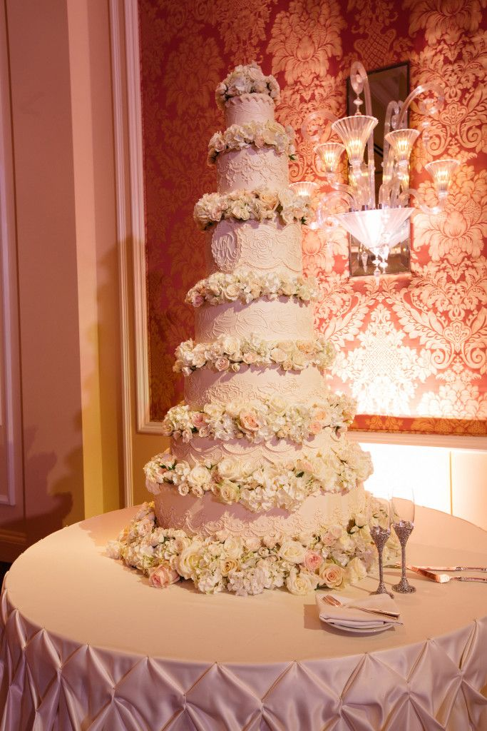 A Sky High Wedding Cake Accented By Delicate Design Work And Fresh Blooms