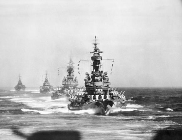 Battleships and heavy cruisers steam in column on 14 July 1945 as they approach the Japanese coast for the bombardment of the iron works at Kamaishi. The USS Indiana (BB 58) is the nearest ship, followed by USS Massachusetts (BB 59) the cruisers USS Chicago (CA 136) and USS Quincy (CA 71). (Courtesy of Newport News Shipbuilding / July 14, 1945)