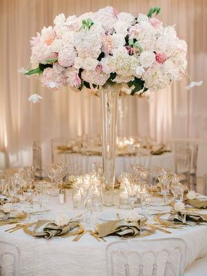 When it comes to choosing wedding centerpieces, most couples first decide if they want tall flower arrangements, low centerpieces, or a mix of high and low designs. While some couples select only small centerpieces to make it easier for guests to converse with one another throughout the celebration, the decision to choose tall flower arrangements is one that will instantly transform the space. There's truly nothing like walking into a grand ballroom or reception tent decoratedwith eleg...