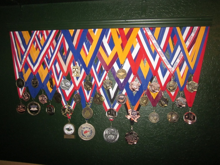 Good way to hang medals. Cut ribbons to correct length and staple to back of a length of wood trim painted to match wall.