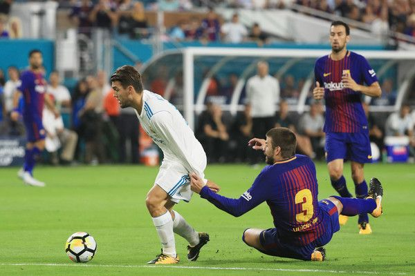 Mateo Kovacic #16 of Real Madrid gets past Gerard Pique #3 of Barcelona on his way to scoring a goal in the first half against the Barcelona during their International Champions Cup 2017 match at Hard Rock Stadium on July 29, 2017 in Miami Gardens, Florida.