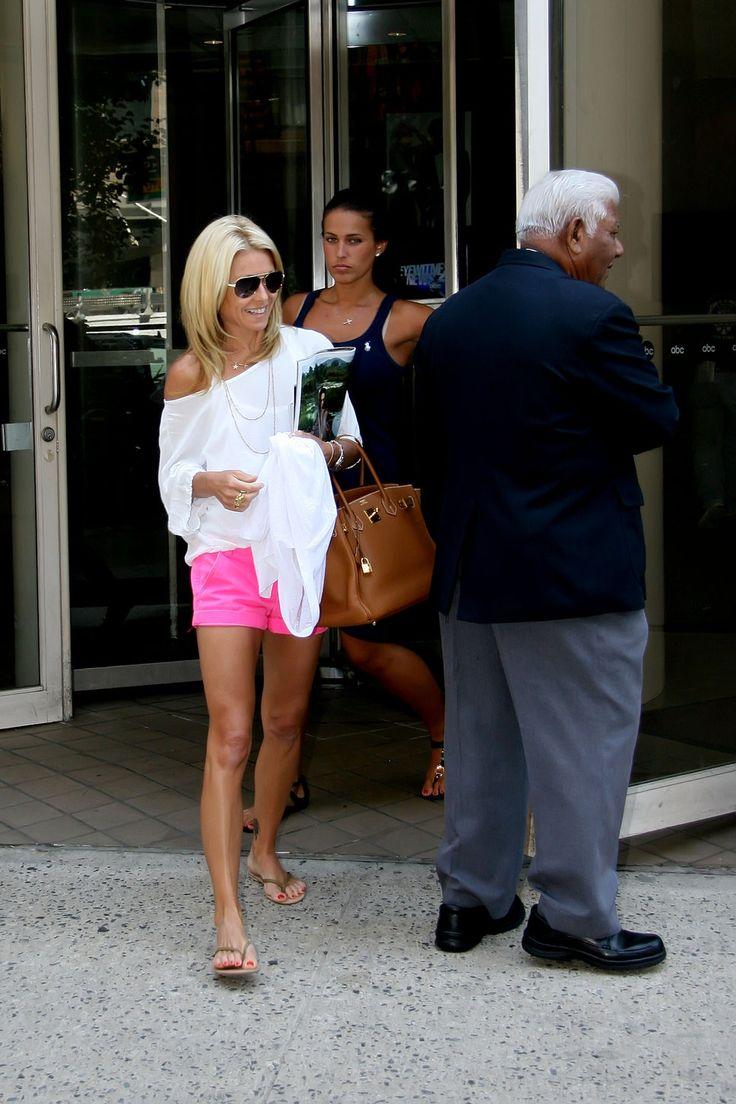 Kelly Ripa off the shoulder white shirt long gold necklaces hot pink shorts neon pink shorts flip flops aviator sunglasses the rachel haircut blonde hair