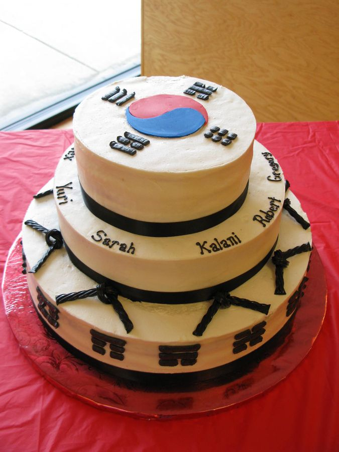 "I did this cake for six people who earned their black belts at the taekwondo school where my son goes.  16"" in chocolate, 12"" in strawberry and 9"" in vanilla, all covered with buttercream.  The South Korean flag symbol is fondant and the rest is buttercream.  I used black Twizzlers for the black belts going around the cake.  Lots of lessons learned here!!"