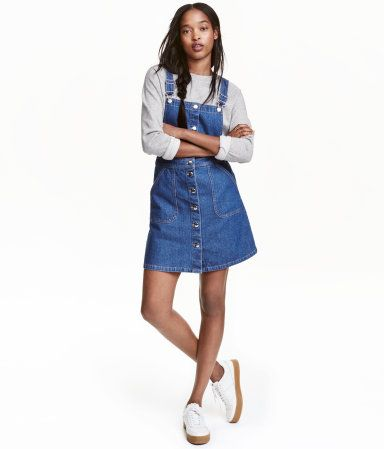 Denim blue. Short bib overall dress in washed denim with adjustable suspenders, front pockets, and buttons at front.