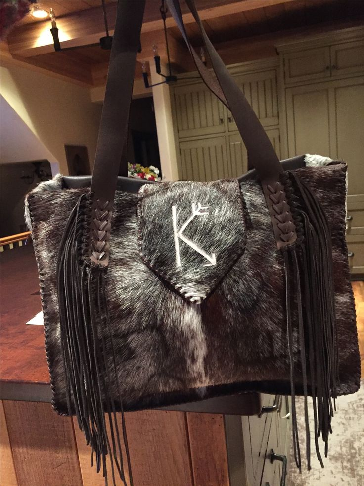 The Buckaroo Diaper Tote stitched in brown leather lace with the owners brand on the flap in white hair on hide. Custom purses and totes from gowestdesigns.us