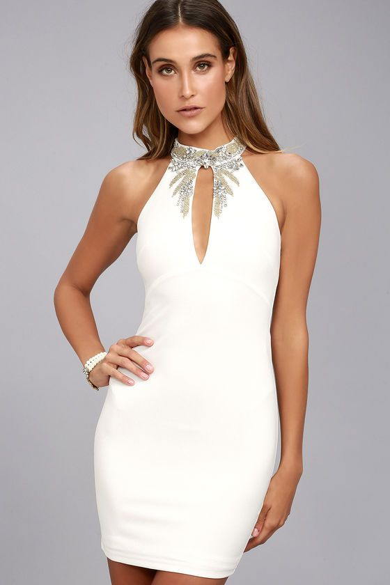 Make a stunning entrance in the Alluring Evening White Beaded Bodycon Dress! Stretch knit shapes a halter neckline, adorned in beautiful clear rhinestones and gold beading. A darted bodice, with keyhole, falls to a figure flaunting bodycon skirt. Hidden zipper/clasp at back.